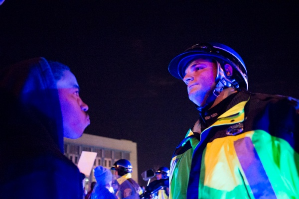 11/25/14 – Medford/Somerville, MA – A protester stares down a police officer during the Indict America rally in Boston on November 25th, 2014. (Nicholas Pfosi / The Tufts Daily)