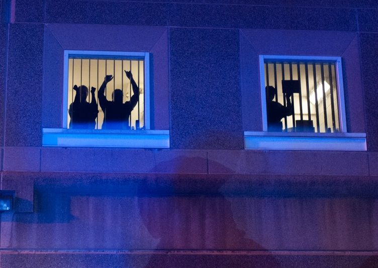11/25/14 – Medford/Somerville, MA – Individuals in the South Bay Correctional Facility animate in their windows during the Indict America rally in Boston on November 25th, 2014. (Nicholas Pfosi / The Tufts Daily)
