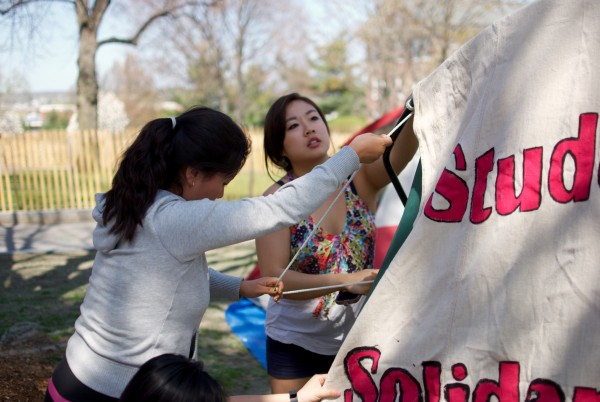 5/3/15 - Medford/Somerville, MA - Two students work to attach signs to the tents. These signs will remain visible to anyone who passes by as long as the camp stays in place.