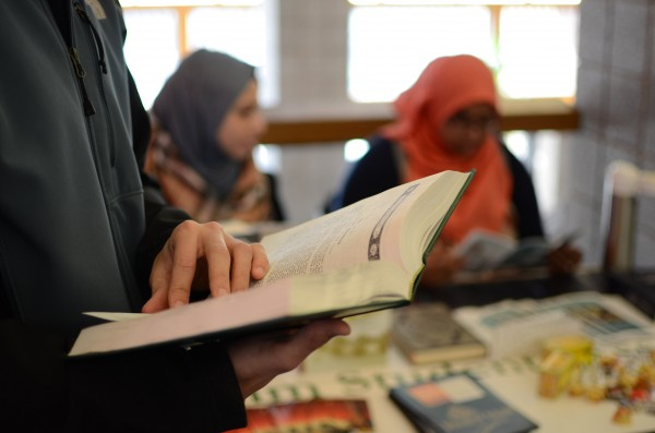 Tufts Muslim Students Association (MSA) hosts Ask A Muslim at the Campus Center to help teach members of the Tufts community about Islam as part of the Spring Into Islam series. A member of the MSA reads the Quran while leading the event on Feb. 17. (Mia Lambert / The Tufts Daily)