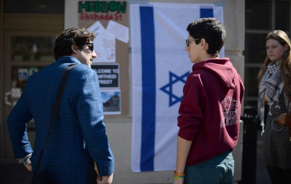 –Members of Students for Justice in Palestine explain the relationship of Hebron to the Israeli occupation of Palestine to a passerby on the Tisch Patio as a part of Israeli Apartheid Week on March 9, 2016. (Sofie Hecht / The Tufts Daily)