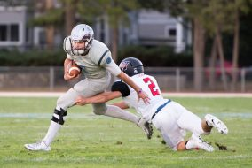 Senior quarterback Alex Snyder lunges ahead of a Wesleyan defender in the game against the Wesleyan University Cardinals on Sept. 24. (Evan Sayles / The Tufts Daily)