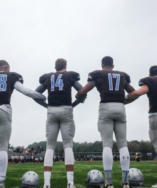 Members of the Tufts football team link arms during the national anthem before the homecoming game against Bates on Oct. 1. (Max Lalanne / The Tufts Daily)