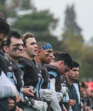 Members of the football team link arms during the national anthem before the homecoming game against Bates on Oct. 1. (Max Lalanne / The Tufts Daily)