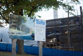 A sign displaying artist's rendition of the finished Central Energy Plant in front of the current construction, pictured on Oct. 5. (Max Lalanne / The Tufts Daily)