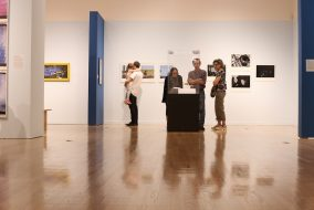 Attendees of the Fall Exhibitions Opening Reception held by the Tufts University Art Gallery examine the new works on Sept. 20.  (Lilia Kang / The Tufts Daily)
