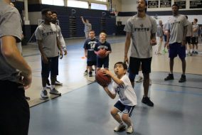 A participant in the free basketball clinic for kids shoots under the watchful eye of Tufts men's basketball players on Oct. 15. (Miranda King-Giannino courtesy of John Skerry)