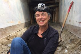 As part of a non-violent protest, ExCollege adjunct professor Norah Dooley sits in Spectra Energy's West Roxbury Lateral Pipeline trench, on Centre Street in West Roxbury, shortly before her arrest on Aug. 31. (Brendan Matulis courtesy Norah Dooley)
