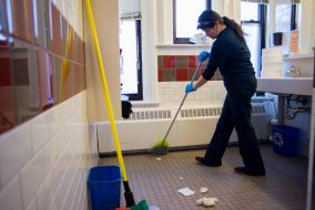 A janitor cleans the first floor bathrooms in West Hall on Nov. 3, 2014. (Nicholas Pfosi / The Tufts Daily Archive)
