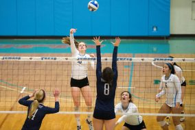 Outside / opposite hitter first-year Maddie Stewart hits the ball over a Middlebury player in the NESCAC championship game against the Middlebury Panthers on Nov. 6. (Evan Sayles / The Tufts Daily)