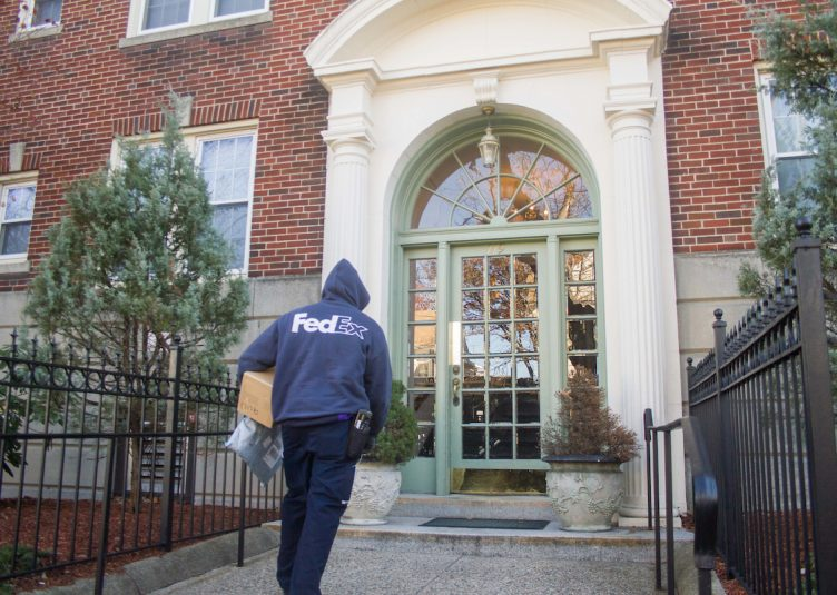 A FedEx deliveryman enters the apartment building located at 119 College Ave on Nov.28. The university attempted to buy the property early in 2015. (Max Lalanne / The Tufts Daily)