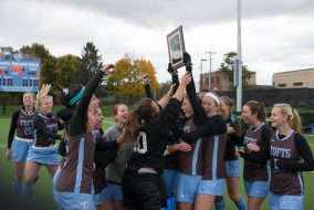 The field hockey team celebrates with its victory plaque after winning the NESCAC championship game against the Middlebury College Panthers on Nov. 6. (Evan Sayles / The Tufts Daily)