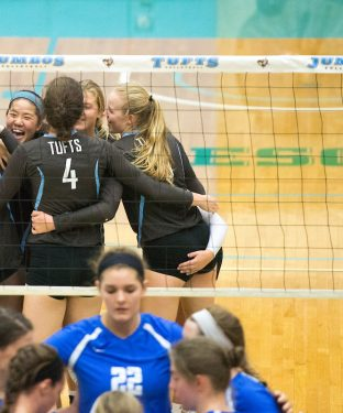 Members of the volleyball team huddle after scoring a point in the first set of the game against the Roger Williams University Hawks on Sept. 14. (Evan Sayles / The Tufts Daily)