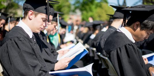 Seniors read the commencement booklet during Tufts University's 158th Commencement on the Academic Quad on May 18, 2014. (Nicholas Pfosi for Tufts University)