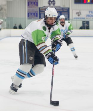 –Junior forward Brian Brown starts to round a corner to move from the corner of the rink to the Camel net in the game against Conn. College on Feb. 5, 2016. (Evan Sayles / The Tufts Daily)