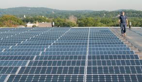 A worker assesses the solar panels on the roof of Dowling Hall on Aug. 20, 2014. (Nicholas Pfosi / The Tufts Daily)