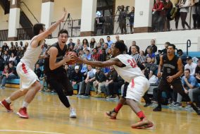 Junior guard Everett Dayton drives to the basket past two Wesleyan defenders on Jan. 20. (Zach Sebek / The Tufts Daily)